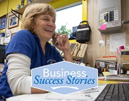 "Woman using a phone. Graphic text reads: ""Business Success Stories"""