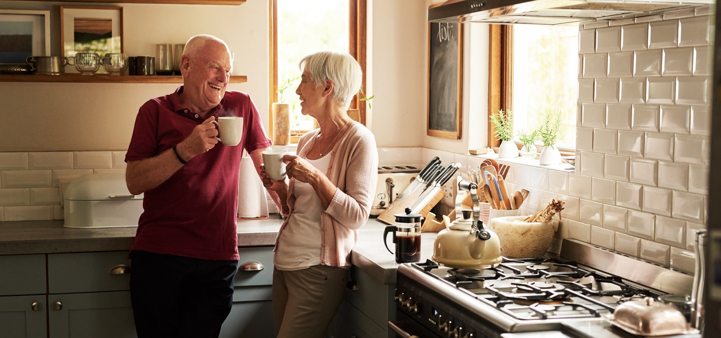 A mature couple drinking coffee together in a kitchen.