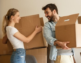 A young couple holding moving boxes.