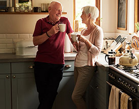 An older couple enjoying cups of coffee in their kitchen